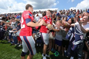 Tom Brady signs an autograph for Ryan Mallett (Photo By David Silverman)