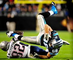 Devin McCourty tackles Greg Olsen (Photo By: Grant Halverson/Getty Images)