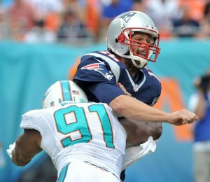 Tom Brady gets hit during the Miami game (Photo By Keith Nordstrom)