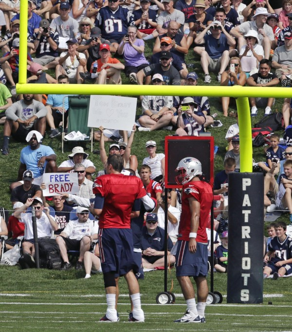"Tom Brady and Jimmy Garoppolo practices in front of a ""Free Brady"" sign. (Photo By: AP Charles Krupa)"