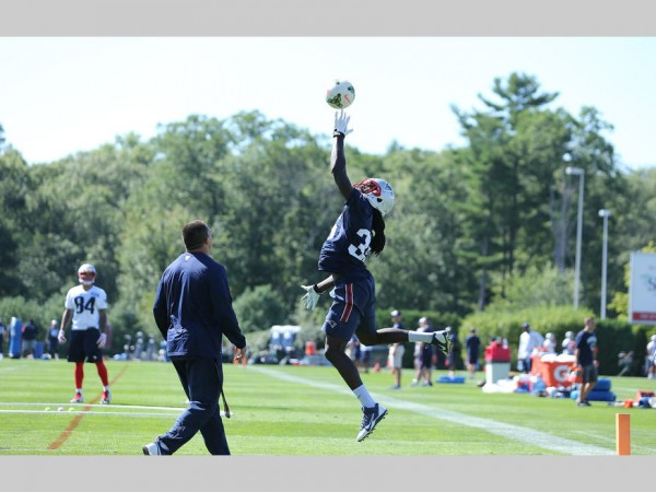 Defensive backs go through a drill involving a volleyball. (Photo By: David Silverman)