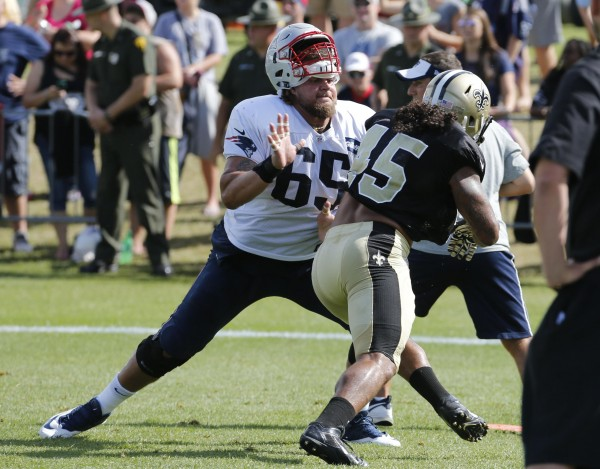 New England Patriots offensive lineman Chris Martin (65) loses his helmet as he blocks New Orleans Saints linebacker Hau'oli Kikaha (45) during a joint practice at the Saints' NFL football training camp in White Sulphur Springs, W.Va., Wednesday, Aug. 19, 2015.  (AP Photo/Steve Helber)