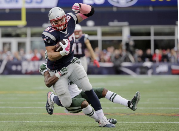 Gronk carries safety Marcus Gilchrist several yards. (Photo By: AP/Steven Senne)