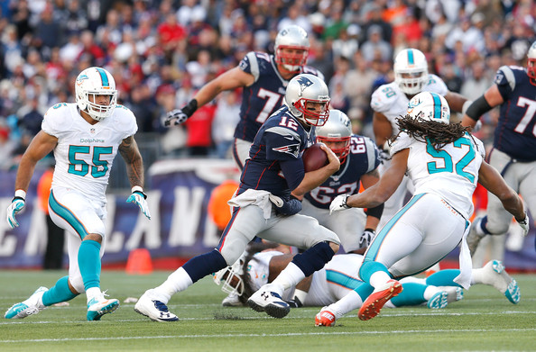 Tom Brady rushes against the Dolphins. (Photo By:  Jim Rogash/Getty Images North America)