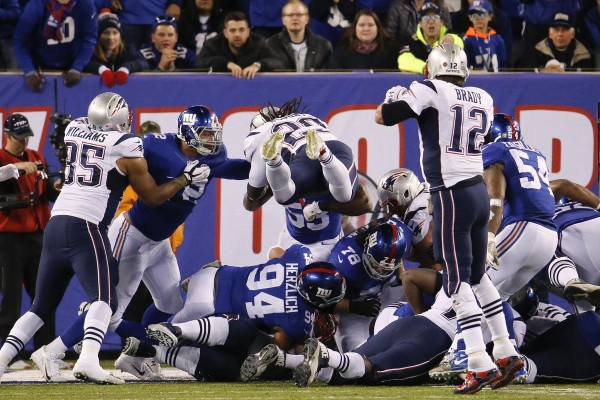 LeGarrette Blount lunges over the defense for a touchdown. (AP Photo/Julio Cortez)